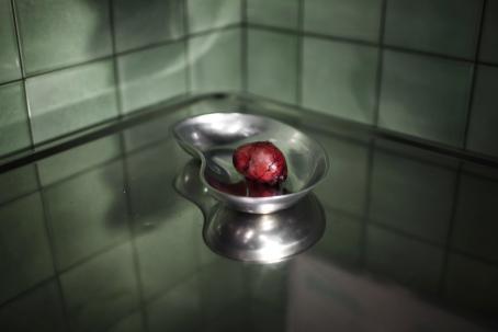 Kliinisen näköisellä metallitasolla on metallinen astia, jossa on punainen möykky.