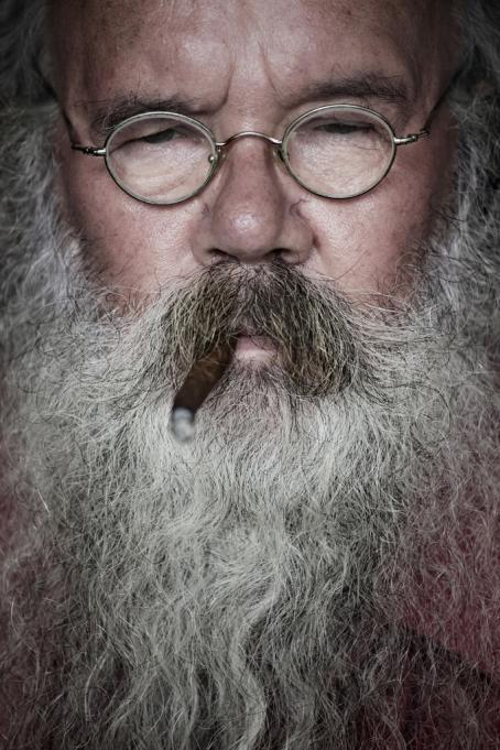 Kuvan täyttävät kokonaan miehen kasvot. Miehellä on pyöreät silmälasit ja tuuhea harmaa parta. Hänellä on suussaan tupakka.