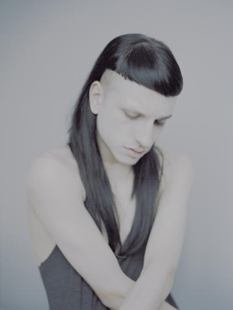 Androgyyni henkilö istuu kädet ristissä edessä ja katse luotuna alaspäin. Hänen tummat hiuksensa ovat edestä lyhyet ja takaa pidemmät.