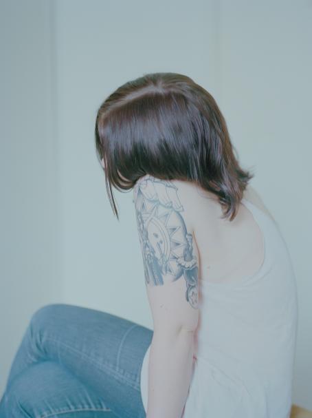 Nuori henkilö istuu sivuttain, hiukset peittävät kasvot. Hänellä on valkoinen toppi ja olkavarressa tatuointi.