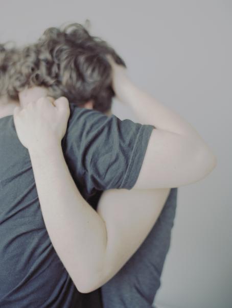 Kaksi henkilöä halaa toisiaan. Heidän kasvojaan ei näy, etualalla ovat heidän käsivartensa ja toisesta näkyy hiukset.