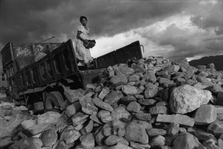 Mustavalkoisessa kuvassa kuorma-auton lavalla oleva valkomekkoinen nainen heittää isoa kiveä pois lavalta. Lavan edessä on iso kasa kiviä.