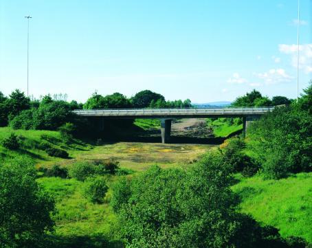 Kuivunut joenuoma, jonka yli menee silta. Ympärillä on vihreää nurmikkoa ja vihreitä puita.