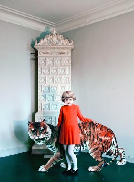 Punamekkoinen lapsi seisoo takanaan tiikeri. Lapsen pää ja tiikeri ovat kiiltokuvamaisia. Heidän takanaan nurkassa seisoo korkea valkoinen koristeellinen kaappi.