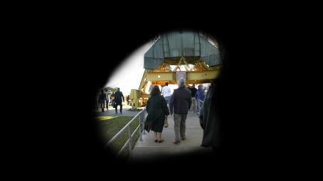 Mustan pinnan keskellä on pyöreähkö aukko, jossa on ihmisiä kävelemässä jonkin ison rakennelman ympärillä.