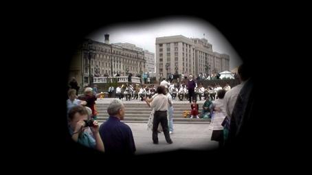 Mustan pinnan keskellä on pyöreähkö aukko, jossa on näkymä jostain torilta tai aukiolta. Taustalla soittaa orkesteri, keskellä tanssii pariskunta ja ympärillä on paljon muitakin ihmisiä.
