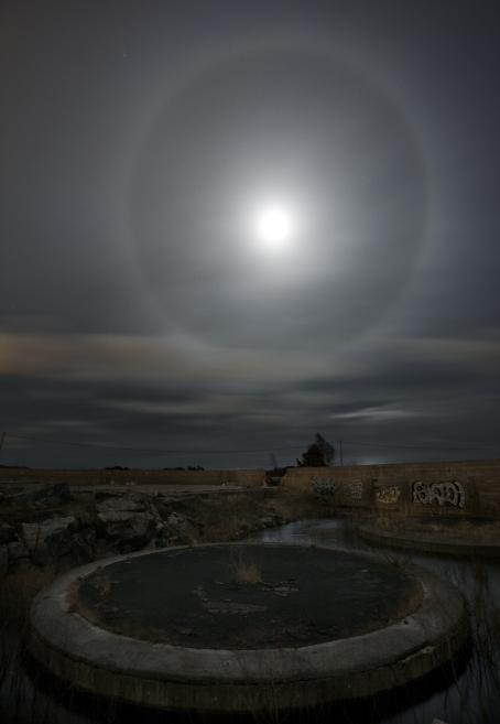 Taivaalla on auringon ympärillä haloilmiö, eli valoympyrä. Etualalla näkyy maassa hämärästi jokin ympyrän muotoinen rakennelma ja graffiteilla koristeltua muuria.