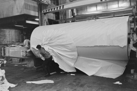 Mustavalkoisessa kuvassa on tehtaassa iso, monta metriä pitkä ja leveä paperirulla, josta työntekijä repii paperia irti.