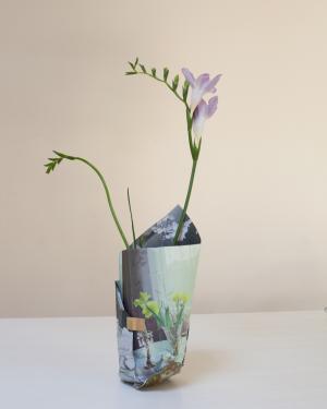 Kukka on purkissa, joka on tehty paperista. Paperissa on kuva kukista maljakossa.