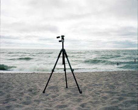 Hiekkarannalla seisoo kameran jalusta. Vedessä on kaksi ihmistä uimassa.