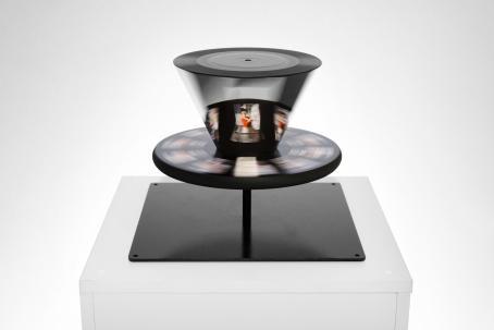 Valkoisella pöydällä on mustan jalustan päällä pyöreä, litteä taso jossa pyörii valokuvia. Litteän tason päällä on kartioimainen uloke, jossa myös näkyy valokuvia.