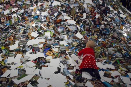 Sadat valokuvat peittävät koko kuva-alan. Osa kuvista on oikeinpäin ja osa väärinpäin. Kuvien päällä konttaa vauva.