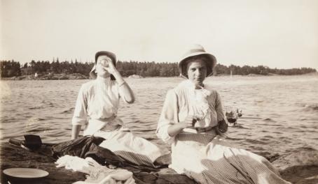 Mustavalkoisessa kuvassa kaksi naista istuvat rantakalliolla. Toinen on juuri juomassa lasista jotain, toisellakin on lasi kädessä. Heillä on päällään pitkät mekot ja hatut.