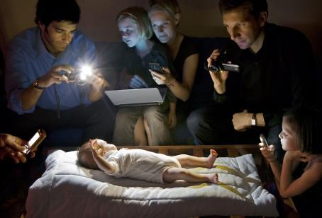 Keskellä sängyllä makaa pieni vauva. Hänen ympärillään on ihmisiä, joilla kaikilla on kädessään joko kamera tai puhelin.