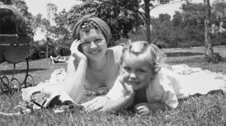 Mustavalkoinen kuva jossa nainen ja lapsi makaavat vierekkäin nurmikolla. Heidän vieressään on lastenvaunut, taustalla näkyy auringonottaja ja metsää.