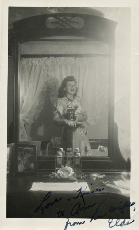 Mustavalkoinen kuva, jonka nainen on ottanut vanhanaikaisella kameralla kampauspöydän peilin kautta. Naisen mekossa on isojen kukkien kuvia ja hänellä on suu auki hymyssä.