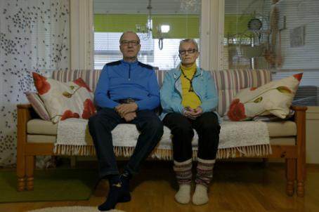 Vanhempi mies ja nainen istuvat sohvalla vierekkäin.
