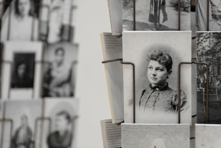 Pyörivässä korttitelineessä mustavalkoisia postikortteja. Kuva on tarkentunut yhteen postikorttiin, jossa on naisen muotokuva.