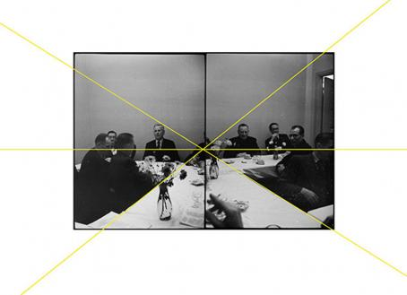 Vierekkäin kaksi mustavalkoista kuvaa, joissa istuu miehiä pöydän ääressä. Kuvien läpi on vedetty suoria keltaisia viivoja, jotka kohtaavat suunnilleen kuvien keskellä.