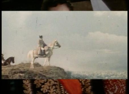 Mies istuu hevosen selässä kalliolla, kaukana alhaalla näkyy kaupungin rakennuksia. Kuvan taustalla näkyy osa ihmisen päästä ja koristeellista takkia.