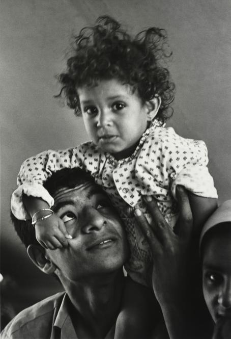 Mustavalkoisessa kuvassa miehen olkapäillä istuu pieni lapsi, joka puristaa miestä poskesta. Mies katsoo ylöspäin lapseen päin.