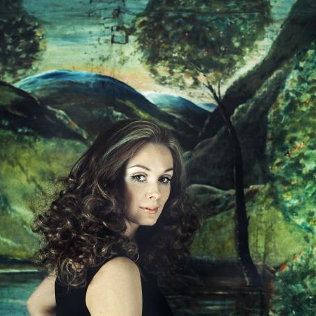Kiharahiuksinen nainen katsoo olkansa yli. Hänen taustallaan on maalaus vihreästä kumpuilevasta maisemasta.