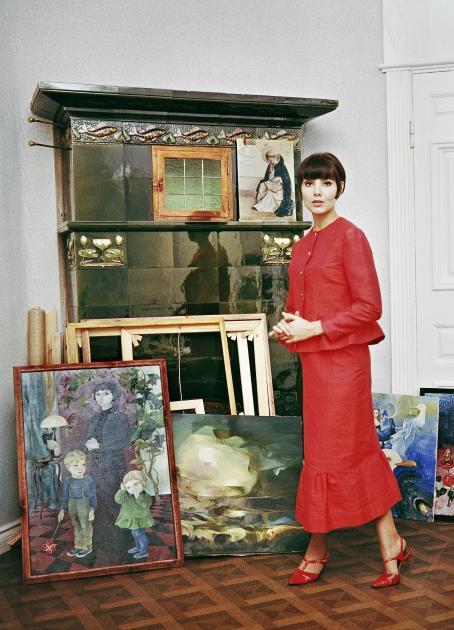 Nainen punaisessa paidassa ja hameessa. Hänen takanaan on takka, jonka edessä lattialla on maalauksia ja tyhjiä kehyksiä.