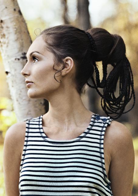 Nainen jolla on mustavalkoraidallinen hihaton paita päällään. Hän on kääntänyt päänsä sivulle.