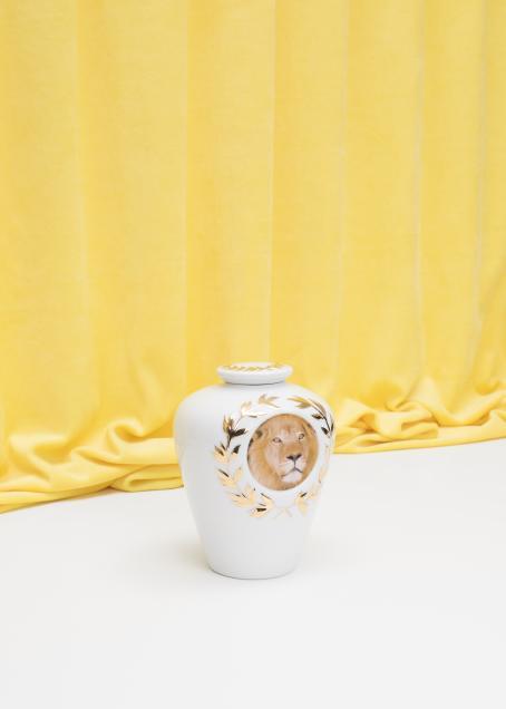 Valkoinen kannellinen purkki, jossa on keltaisia oksakuvioita ja pyöreä leijonan kuva. Taustalla on keltainen verho, joka on vähän kasautunut pöydälle.
