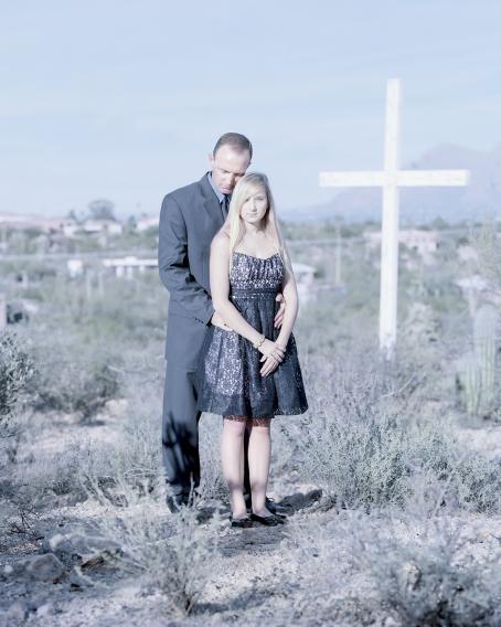 Mies ja nainen seisovat ulkona. Miehellä on puku ja naisella musta mekko. Mies on naisen takana, hän on laittanut kätensä naisen vyötärölle. Heidän takanaan vähän kauempana on iso valkoinen risti.
