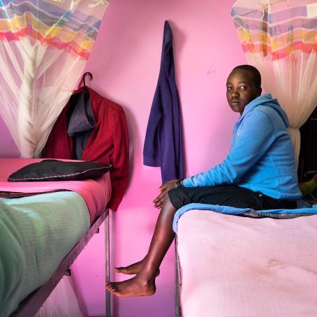 Tummaihoinen tyttö istuu kerrossängyn yläpatjalla jalat roikkuen ilmassa. Hänellä on päällään sininen huppari. Takana oleva seinä on vaaleanpunainen.