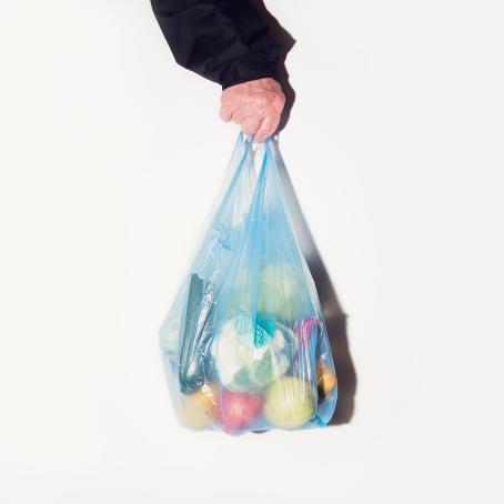 Valkoista taustaa vasten yläreunasta tulee käsi, joka pitelee sinistä läpinäkyvää muovikassia, missä on hedelmiä ja vihanneksia.