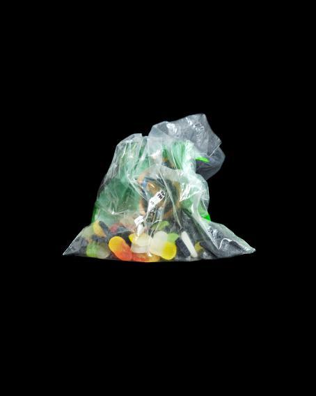 Mustaa taustaa vasten muovipussi, jossa on karkkeja. Muovipussin toiselta puolelta voi erottaa Finnkinon logon.
