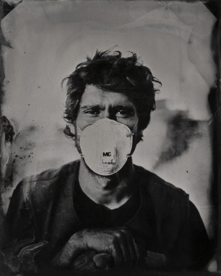 Mustavalkoisessa kuvassa on mies, jolla on hengityssuojain kasvoillaan.