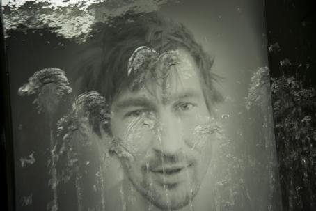 Mustavalkoisessa kuvassa miehen kasvot, joiden päällä näkyy heikosti kukkien muotoja.