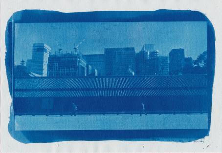 Sinisävyinen kuva, jossa näkyy korkeita rakennuksia ja etualalla kävelee kaksi ihmistä.