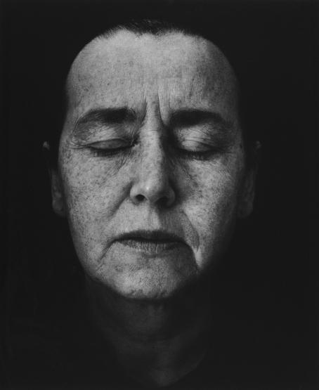 Mustavalkoisessa kuvassa naisen kasvot. Naisen silmät ovat kiinni. Hänen hiuksensa ja olkapäänsä jäävät varjoon.
