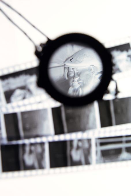 Negatiiveja, jotka ovat sumeita, mutta joista yksi näkyy suurennuslasin läpi. Siinä näkyy kahden ihmisen kasvot.