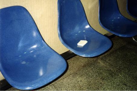Rivissä muovisia sinisiä tuoleja. Yhdellä tuoleista on taiteltu nenäliina.