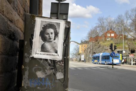 """Seinän vieressä olevaan laatikkoon on teipattu paperi, jossa on mustavalkoinen naisen kuva ja sen alla teksti """"Har du sett denna kvinna?"""". Taaempana näkyy bussipysäkki jolle bussi on pysähtynyt."""