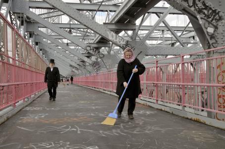 Nainen seisoo sillalla luuta kädessään. Sillassa on paljon graffiteja.