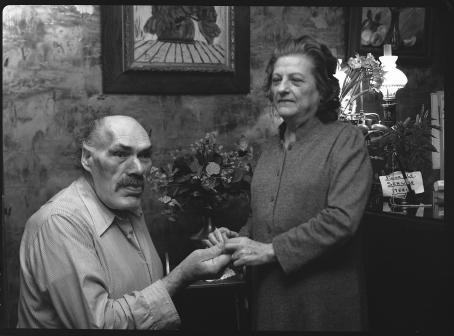 Mustavalkoisessa kuvassa on mies ja nainen. Mies istuu, nainen seisoo ja pitää kiinni miehen käsistä.