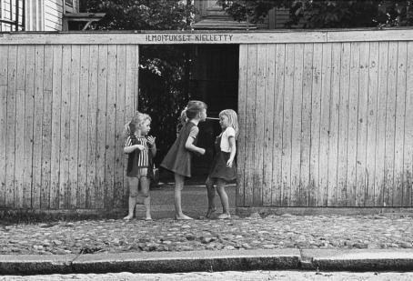 """Mustavalkoisessa kuvassa mukulakivikadulla, puisen aidan keskellä olevan oviaukon edessä seisoo kolme pientä tyttöä. Yksi on kumartunut hiukan toisen puoleen, joka taas on kääntynyt vähän poispäin. Kolmas katsoo vierestä. Oviaukon yläpuolella lukee """"Ilmoitukset kielletty""""."""