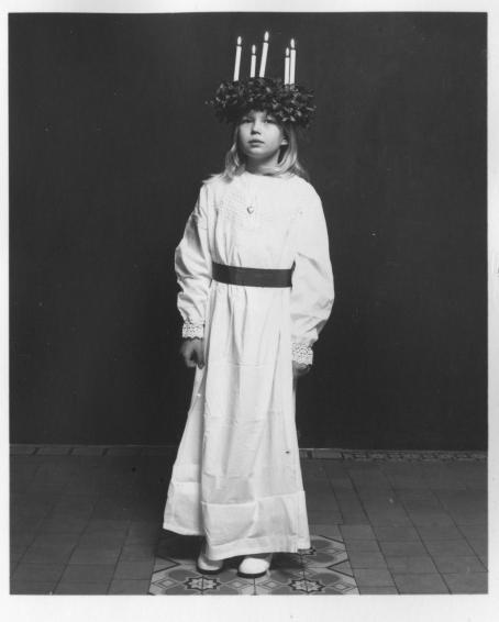 Mustavalkoisessa kuvassa Lucia-neito. Hänellä on valkoinen kaapu jossa on vyö, ja päässä seppele, jossa on kynttilöitä palamassa.