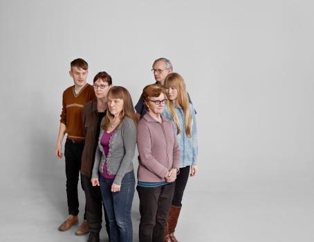 Kuvassa on kuusi aikuista ihmistä. He seisovat osittain selkä toisiinsa päin.