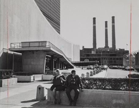 Mustavalkoisessa kuvassa mies ja nainen istuvat matalan kiviaidan päällä. Heidän vieressään on iso rakennus. Taaempana näkyy tehtaiden piippuja. Kuvan molemmissa reunoissa on punainen pystyviiva.