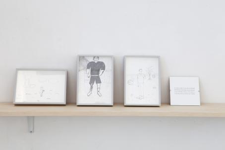 Vaaleanruskealla hyllyllä on neljä kehystä. Kolmessa niistä on piirustuksia, jotka näyttävät lasten tekemiltä, ja yhdessä on tekstiä josta ei saa selvää.