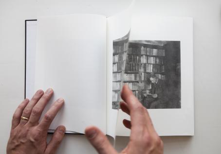 Kädet selaavat kirjaa. Kirjassa on mustavalkoinen kuva, jossa mies istuu ison kirjahyllyn edessä lukemassa kirjaa.