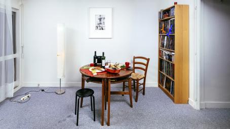 Pyöreä pöytä, jossa on kesken kahden ihmisen ateria. Seinällä on kirjahylly ja taulu, jossa näkyy talon seinällä olevat tikkaat ja niissä roikkuvat miehet.