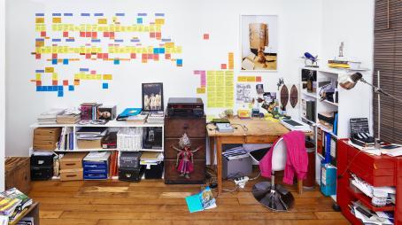 Huone, jossa on työpöytä, hyllyillä papereita ja kansioita, seinälle liimattuna paljon muistilappuja. Pöydän yläpuolella on taulu jossa on kissa.